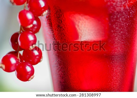 close-up of water droplets on a glasses with alcohol cocktail with cranberry juice on a table in a restaurant with a creative decoration of pieces of orange and fresh berries. soft focus - stock photo