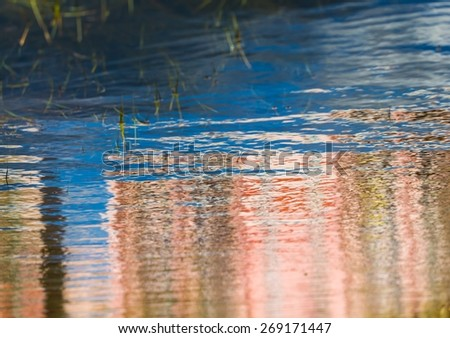 close up of water surface with ripples. sky with clouds, building or tree reflected in water. - stock photo