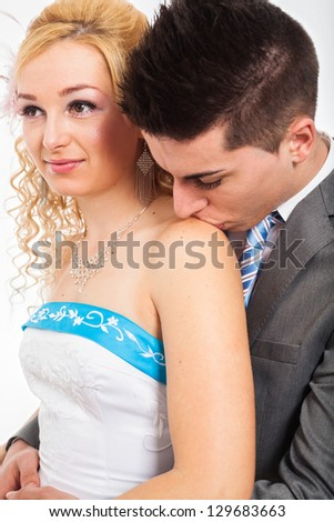 Close up of wedding couple hugging and kissing on shoulder. - stock photo