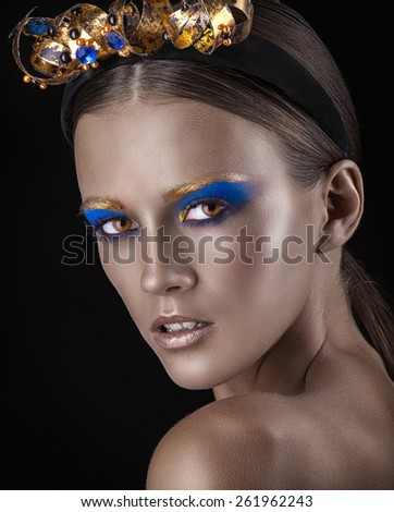 Close-up of well-groomed young woman with fashion makeup on a dark background - stock photo