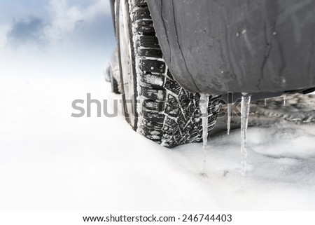 Close up of wheel of car in snow in winter - stock photo