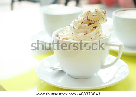 Close up of whipped cream topped with chocolate on hot cocoa drink. - stock photo