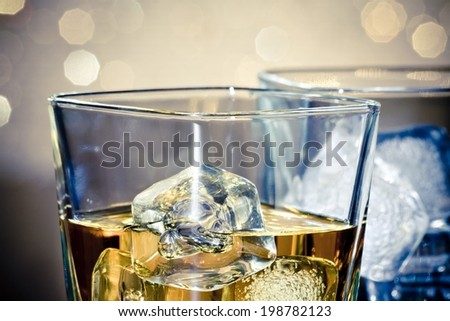 close-up of whiskey glasses on blue light and bokeh background - stock photo