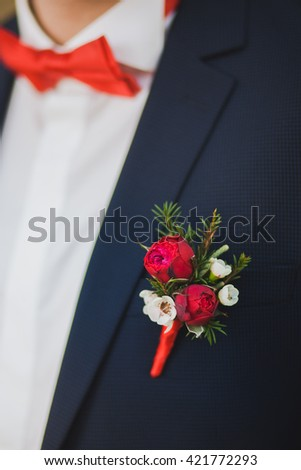 Close up of white and red rose corsage on man suit. Beautiful boutonniere pinned on man in blue suit, White shirt and red bowtie. Groom or graduate. - stock photo