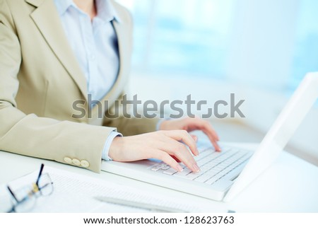 Close-up of white collar worker typing on laptop - stock photo