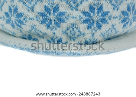 Close-up of White Knitted Winter Ski Wool Hat With Pom-Pom and Blue Jacquard Pattern Isolated on White Background - stock photo