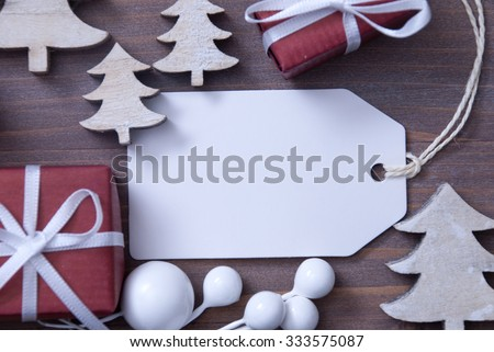 Close Up Of White Label With Ribbon, Red Christmas Gift Or Present, Ribbon And Christmas Tree. Christmas Decoration Or Card On Wooden Background. Copy Space Or Free Text For Advertisement. - stock photo