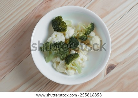 Close up of white radish with broccoli in a bowl on a wooden table.  - stock photo