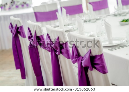 Close-up of white wedding chairs with purple ribbon - stock photo