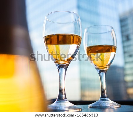 Close up of white wine bottle and wine glasses  - stock photo