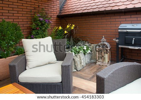 Close-up of wicker chair on modern terrace - stock photo