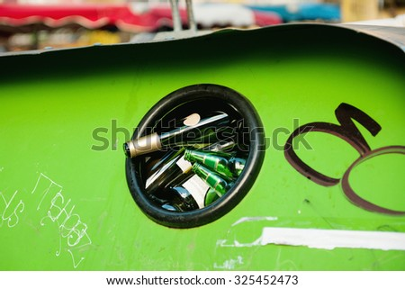 Close-up of wine and beer bottles in a bottle bank on the street - stock photo