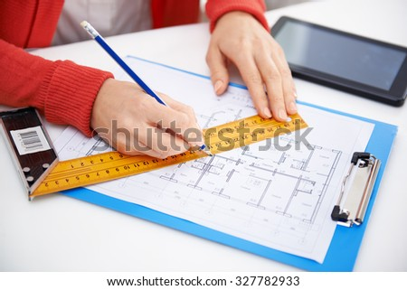 Close-up of woman architect drawing and measuring construction plan in her office. Woman designer with ruler and pencil working on house sketch.  - stock photo