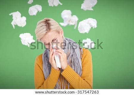 Close up of woman blowing her nose against blue background - stock photo
