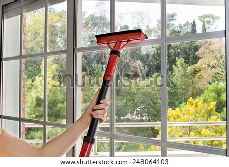 close up of woman cleaning window glass with steam - stock photo