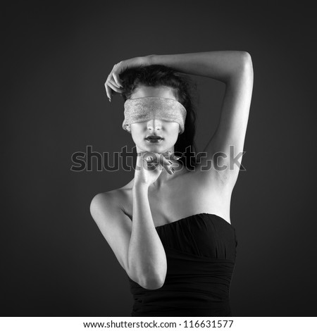 Close up of woman constrained by gauze ring on eyes. Black and white conceptual image. - stock photo