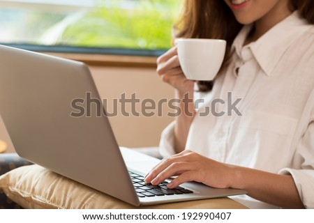 Close-up of woman drinking coffee while using laptop - stock photo