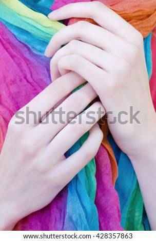 Close up of woman elegant thin hands and long fingers holding colorful fashionable scarf. - stock photo