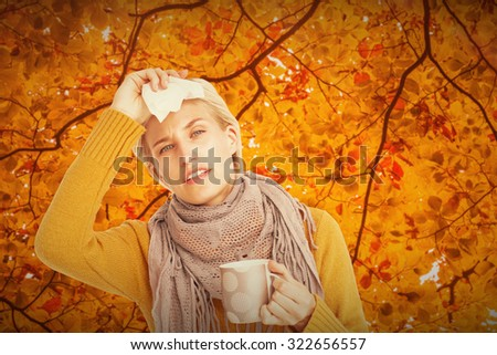 Close up of woman feeling her forehead against autumn scene - stock photo