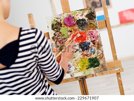 Close-up of woman hand drawing picture with brush and colorful oil paints. Young female painter working at easel in her artistic studio.  - stock photo