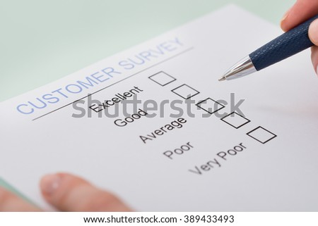 Close-up Of Woman Hand Filling Customer Satisfaction Form - stock photo