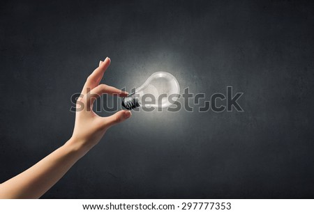 Close up of woman hand holding glass light bulb - stock photo