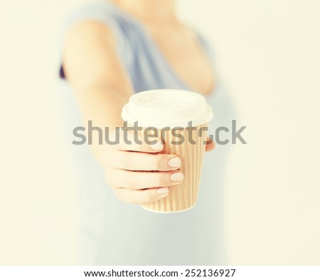 close up of woman hand holding take away coffee cup - stock photo