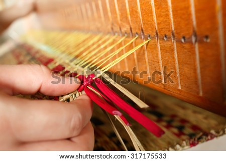 Close up of woman hand on woven mat - stock photo