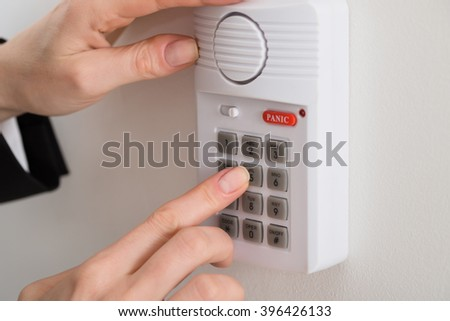 Close-up Of Woman Hand Pressing Button On Security System - stock photo