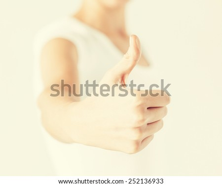 close up of woman hand showing thumbs up - stock photo