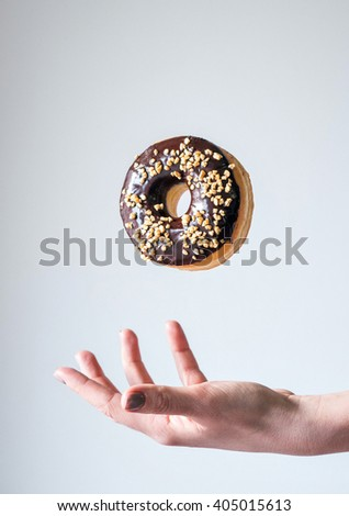 Close up of woman hands holding donut on white background - stock photo