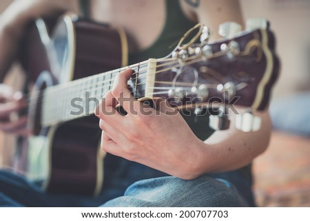close up of woman hands playing guitar at home - stock photo