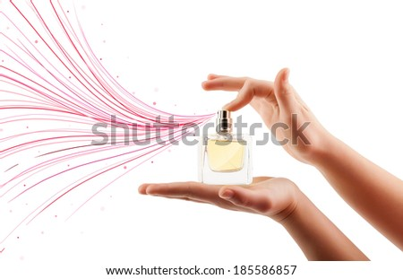 close up of woman hands spraying colorful lines from beautiful perfume bottle - stock photo