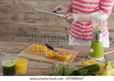 Close up of woman hands with tablet pc, fruits and fresh juice sitting at table - stock photo