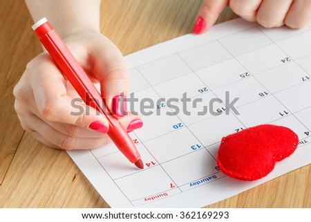 close-up of woman highlighting date on calendar - stock photo