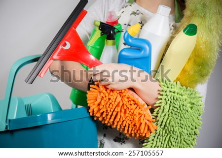 Close-up of woman holding a lot of cleaning tools - stock photo