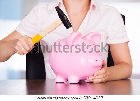Close-up Of Woman Holding Hammer Over Piggybank - stock photo