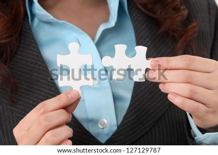 close up of woman holding puzzle pieces - stock photo