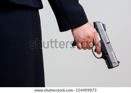 Close up of woman in business suit holding a gun back side - stock photo