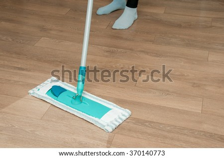 Close up of woman legs with mop cleaning floor at home - stock photo