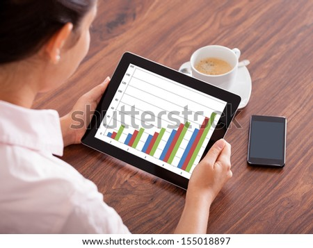 Close-up Of Woman Looking At Graph On Digital Tablet And Mobile Phone - stock photo