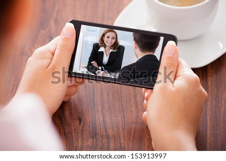 Close-up Of Woman Looking At Video Conference On Mobile Phone - stock photo