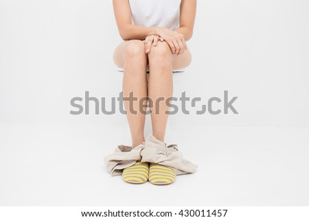 Close up of woman on toilet in morning - stock photo