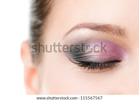 Close up of woman's closed eye with makeup of pink and grey eye shades, isolated on white - stock photo
