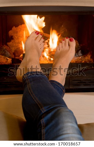 close up of woman's feet in front of an open fire - stock photo