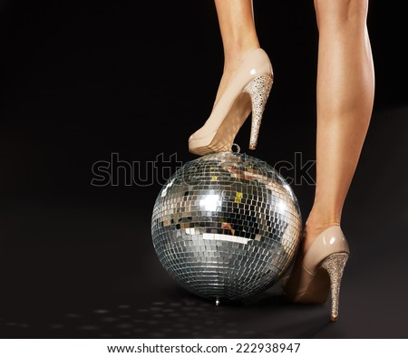 Close-up Of Woman's Foot Wearing Stilettos Over Disco Ball - stock photo