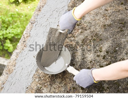 Close-up of woman's hand holding a trowel, applying mortar - stock photo