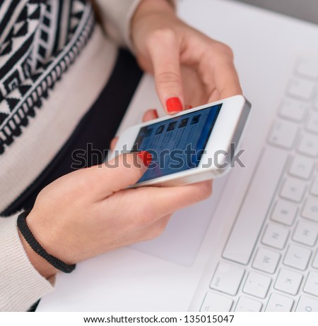 Close-up Of Woman's Hand Holding Cell Phone, Indoors - stock photo