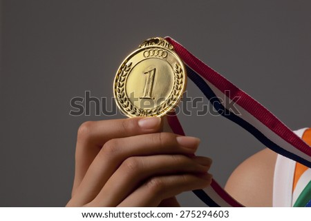 Close-up of woman's hand holding gold medal isolated over gray background - stock photo