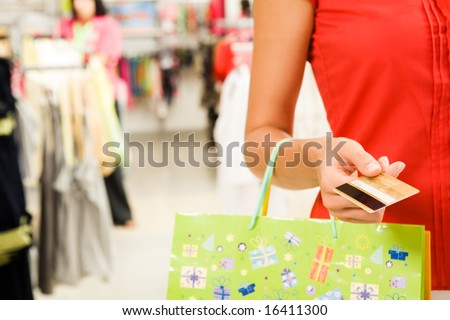 Close-up of womanâ??s hand holding plastic card while going shopping in the mall - stock photo